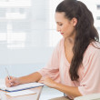 Concentrated businesswoman writing on clipboard — Stock Photo #39187405