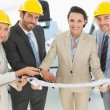 Stock Photo: Confident architects with hard hats and blueprint