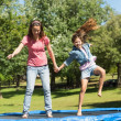 Happy girl and mother jumping high on trampoline in park — Stock Photo