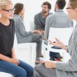Stock Photo: Group therapy session with therapist and client in foreground