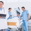 Doctors holding reports by patient at hospital — Stock Photo #39188433