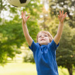 Stock Photo: Smiling young boy playing with ball in park