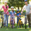 Family of four with bicycles in the park — Stock Photo #39188863