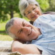 Close-up portrait of a senior couple lying at park — Stock Photo