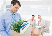 Businessman carrying his belongings with colleagues in backgroun — Stock Photo