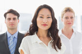Serious businesswoman in front of her team — Stock Photo