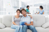 Couple using digital tablet with colleagues at creative office — Stock Photo