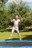 Happy girl jumping high on trampoline in park — Stok fotoğraf