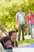 Kids in tent with couple in background at park — Stock Photo