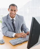 Smiling businessman using computer at office — Stock Photo