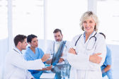 Smiling female doctor with colleagues in meeting — Stock Photo