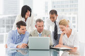 Happy business people gathered around laptop looking at it — Stock Photo