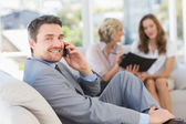 Businessman on call with female colleagues in background — Stock Photo