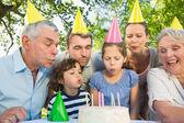 Uitgebreide familie waait taart buitenshuis — Stockfoto