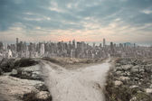 Dusty path leading to large city — Stock Photo