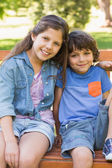 Young boy and girl sitting on park bench — Stok fotoğraf
