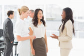 Businesswomen speaking together in conference room — Stock Photo