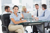 Young businesswoman with colleagues discussing in office — Stock fotografie