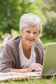 Smiling senior woman using laptop at park — Stock Photo