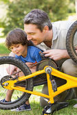 Father and son fixing bike — Стоковое фото