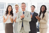 Business team standing and clapping at the camera — Stock Photo