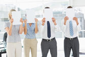 Business people with blank paper in front of faces in office — Stock Photo
