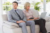 Well dressed man with woman using laptop at home — Stock Photo