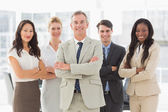 Business team smiling at camera with arms folded — Stock Photo