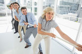 Group of business people pulling rope in office — Stock Photo