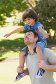 Smiling man carrying son on his shoulders in park — Stock Photo