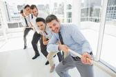 Grupo de empresarios tirando la cuerda en oficina — Foto de Stock