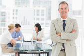 Happy businessman looking at camera while staff discuss behind him — Stock Photo