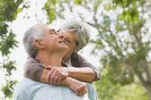 Senior woman embracing man from behind at park — Stock Photo