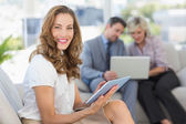 Businesswoman using digital tablet with colleagues using laptop — Стоковое фото