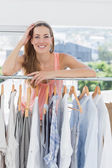 Beautiful female fashion designer with rack of clothes in store — Stock Photo