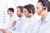 Business colleagues with headsets in a row — Stockfoto