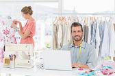 Man using laptop with fashion designer working at studio — Stock Photo