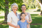 Smiling woman with grandmother and granddaughter at park — Foto Stock