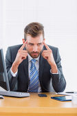Businessman with severe headache at office desk — Stock Photo