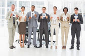 Happy business team holding up letters spelling support — Stock Photo