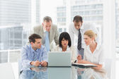 Business people gathered around laptop talking — Stock Photo
