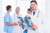 Doctor examining x-ray with colleagues standing behind — Stock Photo