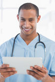 Happy handsome doctor holding digital tablet — Stock Photo