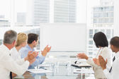 Business people applauding blank whiteboard in conference room — Stok fotoğraf