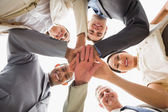 Cheerful business team looking down at the camera with hands tog — Stock Photo