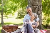 Senior man embracing woman from behind at park — Stock Photo