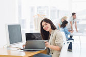 Casual woman working at desk with colleagues behind in office — Stock Photo