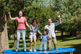 Happy family jumping high on trampoline in park — Stock Photo