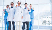 Doctors gesturing thumbs up at hospital — Stock Photo
