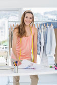 Smiling female fashion designer working in studio — Stock Photo